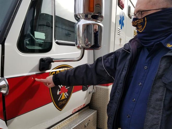 Canton Fire Department Battalion Chief Steven Henderson shows a spot where gunfire struck an ambulance Thursday. Lori Steineck / The Canton Repository