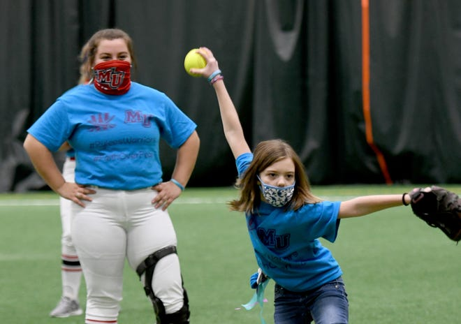 Rylee Abbuhl, 10, of Canton, throws out the first pitch for the Rylee's Warriors scrimmage between Walsh University and Malone University softball teams followed by signing a commitment letter.