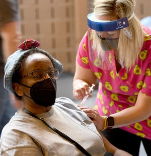 Renee Trawick of Canton receives her first dose of the Moderna COVID-19 vaccine from volunteer, Erin Garner, RN, during the recent Canton City Public Health vaccine clinic at Canton Memorial Civic Center.  Thursday, Februay 25, 2021.