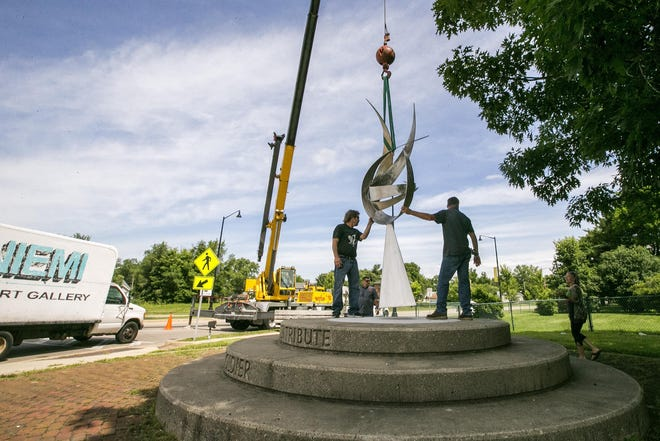 """Kenosha, Wisconsin artist Bruce Niemi, left, helps a Ware Crane & Rigging employee install his sculpture """"The Glorious Ascent"""" on June 25, 2018, at the northeast corner of the Auburn Street roundabout."""