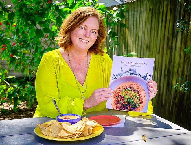 "Local author and photographer Jennifer Jordan holds a copy of her new book ""Veggin in St. Augustine"" at the Back 40 Restaurant in St. Augustine."