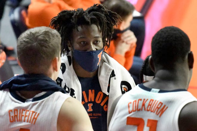 Illinois guard Ayo Dosunmu talks with teammates forward Zach Griffith (4) and center Kofi Cockburn (21) on the sideline, in the second half against Nebraska Thursday in Champaign. Dosunmu did not play due to a broken nose. (AP Photo/Holly Hart)