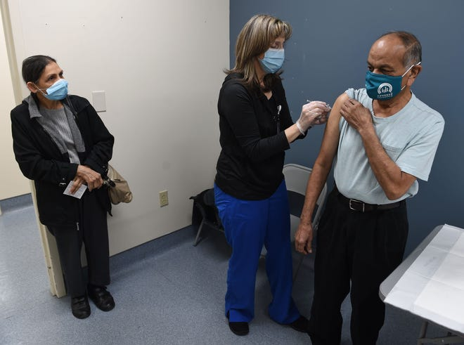 Registered nurse Pamela Ford, center, gives Sumant Patel, of Southington, the Pfizer COVID-19 vaccine at Hartford HealthCare's mega-vaccine site at 1 Liberty Square in New Britain Thursday. Looking on at left is Sumant's wife Laxmi Patel, who also received the vaccine.
