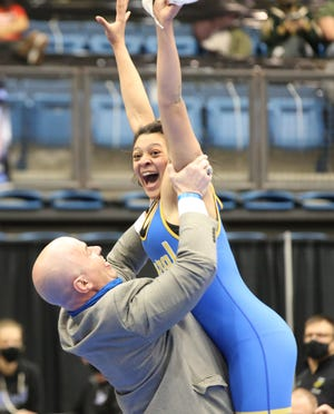 Washburn Rural's Rebekah Smith is hoisted into the air by Junior Blues coach Damon Parker after winning the 155-pound state championship at Thursday's girls Division I state tournament at Hartman Arena in Park City. Rural also won its second-straight team championship.