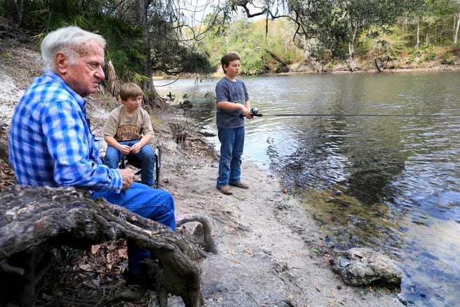 Charlie Norris, then 10, fishes from the shore of the Santa Fe River with his brother, Gage, as they spend the afternoon with their grandfather, Jim Norris, at the Santa Fe River Boat Ramp park in High Springs in February 2020.