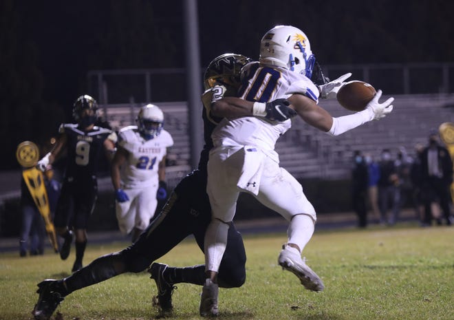 Eastern Guilford defensive back Marcus Bynum, right, intercepts a Williams pass in the end zone as Bulldogs receiver Xavion Jones wraps him up.