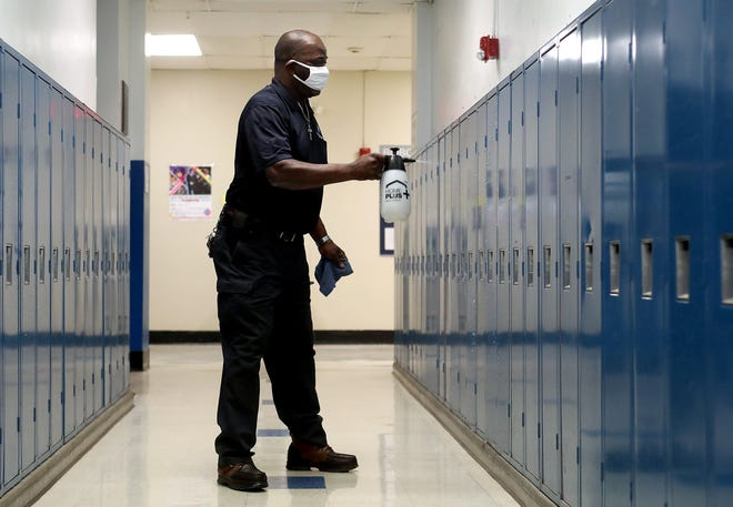 Grandview Heights Shools custodian Franklin Bright sanitizes rows of lockers after classes ended for the day at Grandview Heights High School on Feb. 24. The district is expected to return to a full-time, all-in schedule March 15.