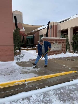 A worker shoves snow and ice off the sidewalk in front of the Waxahachie Civic Center during last week's winter storm. The City Council had lots of praise for its employees who worked tirelessly to keep the city safe.