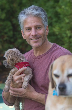 """Co-founder Tom Rosedale, holding Coco, is known as Top Shelf Dog's """"legal beagle,"""" since he spent the majority of his career practicing law. Throughout his career he's founded a number of successful companies, according to his biography."""
