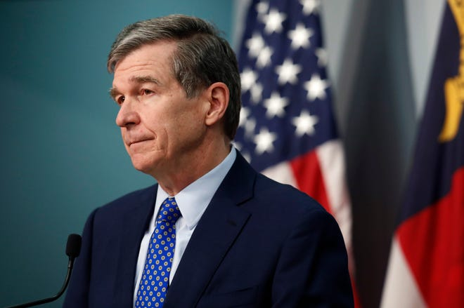N.C. Gov. Roy Cooper listens to a question during a briefing at the Emergency Operations Center in Raleigh, N.C., Wednesday, Feb. 24, 2021. (Ethan Hyman/The News & Observer via AP)