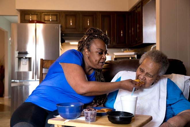 Guselyn Bobb, 58, helps her mother, Lena Bobb, 87, with her lunch on Friday, Feb. 26, 2021 at their home in the Pleasant Run Farm neighborhood of Springfield Township. Guselyn Bobb said she had been trying to get her mother vaccinated for about two months and that her primary care physician was able to secure a Moderna COVID-19 vaccine for her, which was administered on Thursday, Feb. 25. Bobb has been unable to be vaccinated despite being her mother's full-time caregiver.