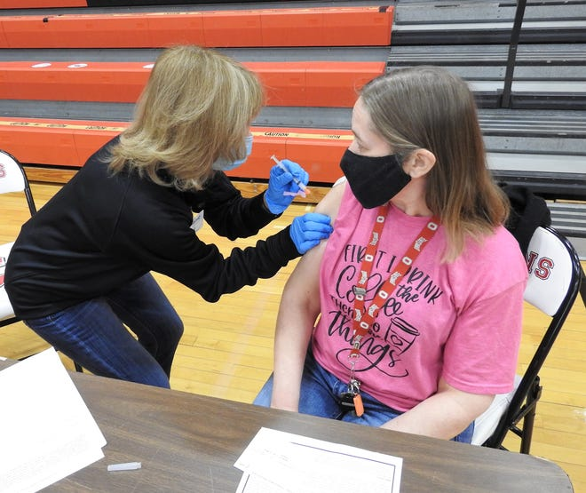 Jeanie Blake of Muskingum Valley Health Centers administers the COVID-19 vaccine to Lana Lawson, a first grade teacher at Coshocton Elementary School. About 450 doses were given to county school employees at a clinic held Friday at Coshocton High School. The second dose will be given in about four weeks at a similar style clinic.