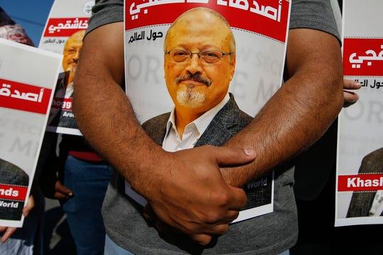 """أشخاص يحملون ملصقات للصحفي السعودي المقتول جمال هاشقجي ، بالقرب من القنصلية السعودية في اسطنبول ، بمناسبة مرور عامين على وفاته ، 2 أكتوبر / تشرين الأول 2020. كُتبت الملصقات باللغة العربية: """"أصدقاء Hashugi حول العالم."""""""