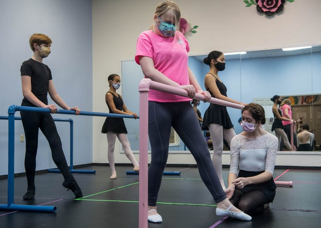 Ballet instructor Emma Stevens teaches Cadie Riley, a 14-year-old visually impaired teen, how to pointe her toes properly during a tendu at the barre at Children's Center for Dance Education in Evansville, Ind., Thursday, Feb. 25, 2021. Ballet students, from left, Robert Hughes, 13, Maya Ragland, 14, and Claire Baba, 13, danced alongside Riley during her formal lesson.