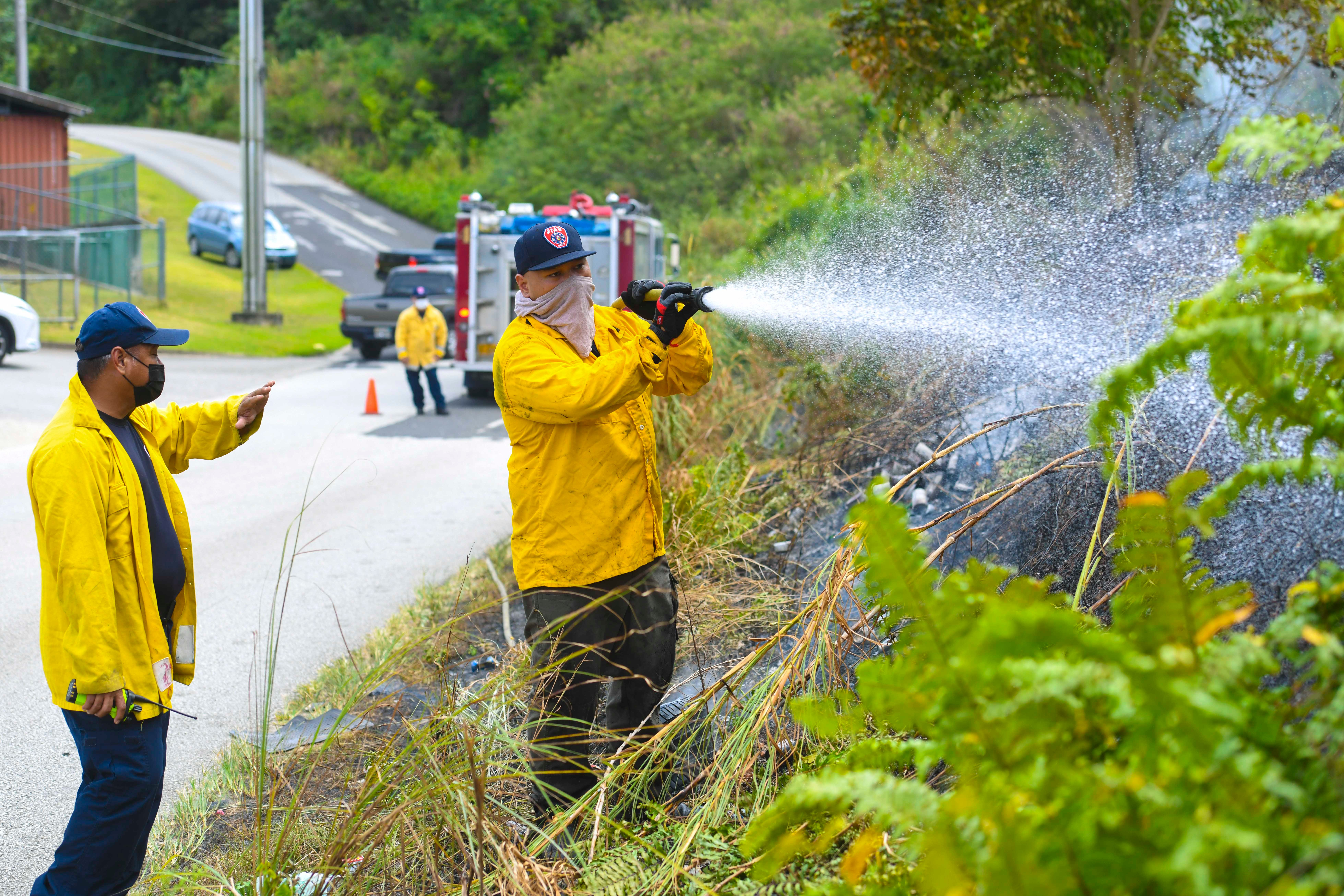 Firefighter Vince Toves, center, extinguishes hot spots at a grass fire along Mendioka Street in Dededo in this Feb. 26 file photo. The National Weather Service issued a fire weather watch for Guam, especially for central and southern areas.