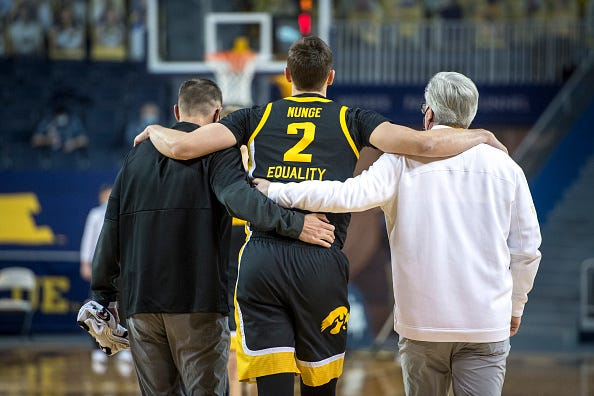 Jack Nunge left Thursday's game at Michigan with 11:49 remaining in the first half. Here, he is helped off the Crisler Center court by trainer Brad Floy, left, and coach Fran McCaffery.
