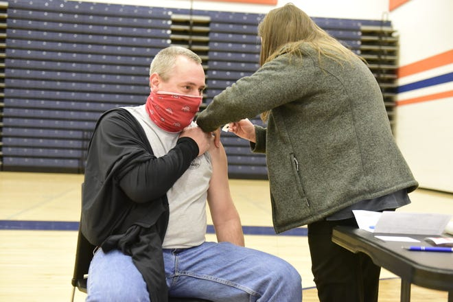 Troy Tunker, a seventh-grade social-studies teacher, gets his COVID vaccine Friday morning at Galion High School.