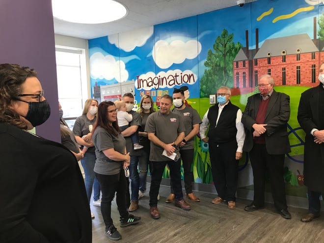 Jodie Perry, president of the Richland Chamber and Economic Development, left, kicks off the ribbon-cutting ceremony Friday at the Imagination Child Care, 100 Park Avenue West with owners Todd and Julie Wurthmann and community leaders. The site was formerly a Huntington Bank.