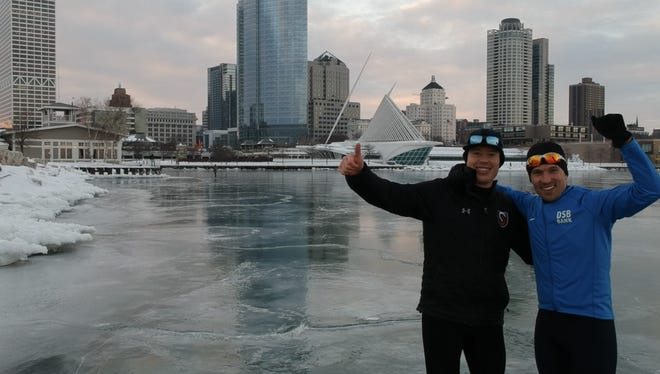 """Brian Hansen (left) and Brent Aussprung stand on the ice on Lake Michigan on Feb. 20 after navigating the """"wild ice"""" of the harbor in Milwaukee."""