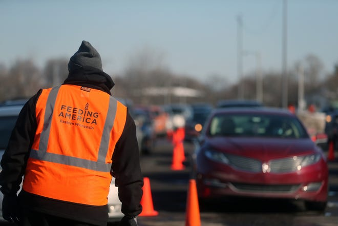 A man from Feed America helps monitor motorists arriving to receive 6,000  turkeys from Meijer during the Feeding America Eastern Wisconsin food distribution event.