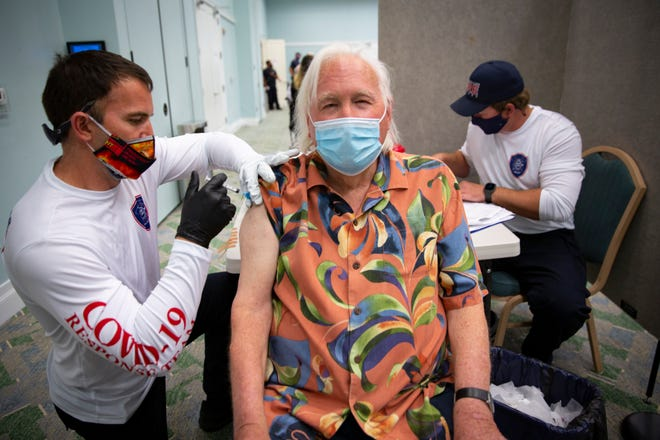 North Collier Fire District Lt. Dustin Gourley, left, administers a COVID-19 vaccine to Gerhard Martin, a seasonal Naples resident from Syracuse, New York, on Feb. 26 at a pop-up vaccination site at the Pelican Bay Community Center in Naples.