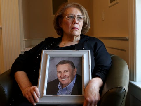 Carol Alamia poses for a picture as she holds an image of her husband, who died from COVID-19.  Monday, Feb. 22, 2021