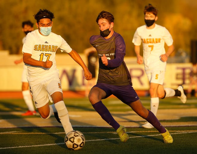 Feb. 11, 2021; Scottsdale, Arizona, USA; Notre Dame Prep's Riley McMenomy (16) dribbles up the pitch against Saguaro's Hector Hernandez (17) during the first half at Notre Dame Prep. Mandatory Credit: Patrick Breen-Arizona Republic