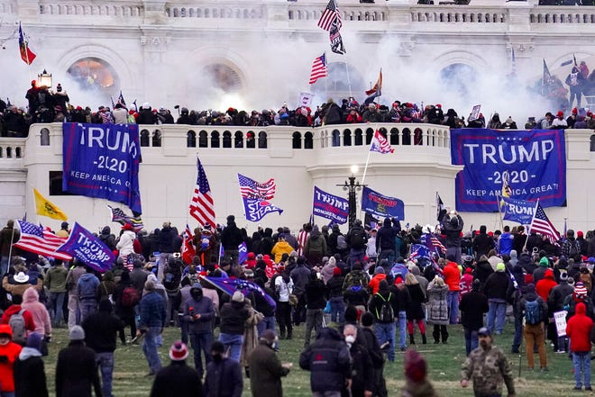 FILE - In this Wednesday, Jan. 6, 2021, file photo, violent rioters supporting President Donald Trump, storm the Capitol in Washington. A faction of local, county and state Republican officials across the country is pushing lies, misinformation and conspiracy theories online that echo those that helped inspire the violent Capitol insurrection, forcing the GOP into an internal reckoning.. (AP Photo/John Minchillo, File)