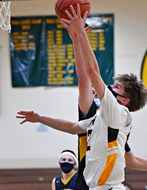 York Catholic's Luke Forjan, right, takes the ball to the basket while Littlestown's Jake Bosley defends during boys' basketball action at York Catholic High School in York City, Thursday, Feb. 25, 2021. Littlestown would win the game 57-41. Dawn J. Sagert photo