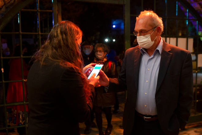 """A man presents his """"green passport,"""" proof that he is vaccinated against the coronavirus, on opening night at the Khan Theater for a performance where all guests were required to show proof of vaccination or full recovery from the virus, in Jerusalem, Tuesday, Feb. 23, 2021. (AP Photo/Maya Alleruzzo)"""