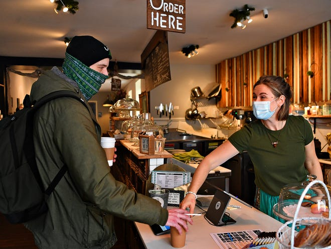 Barista Evelyn Price, right, serves Stephen Willson, of York City, his Americano and Monkey See, Monkey Do smoothie to-go at Molly's Courtyard Cafe in York City, Friday, Feb. 26, 2021. Dawn J. Sagert photo