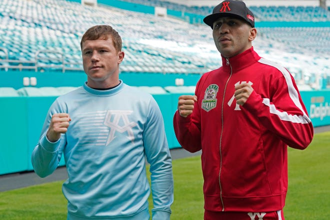 Canelo Alvarez, left, and Avni Yildirim pose for photos at Hard Rock Stadium on Monday in Miami Gardens, Florida. The two will fight Saturday night.