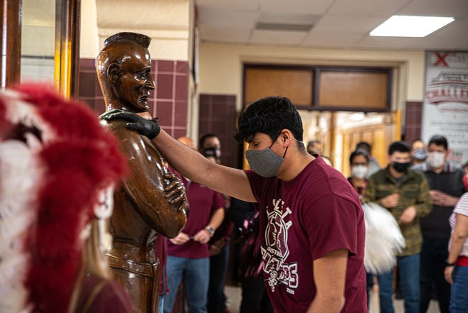 An Ysleta basketball player places his right hand of the right shoulder of the school's Kaw-Liga. Ysleta High School's basketball team participated in the Kaw-Liga ritual in the main hall of Ysleta High School on Friday, Feb. 26, 2021.