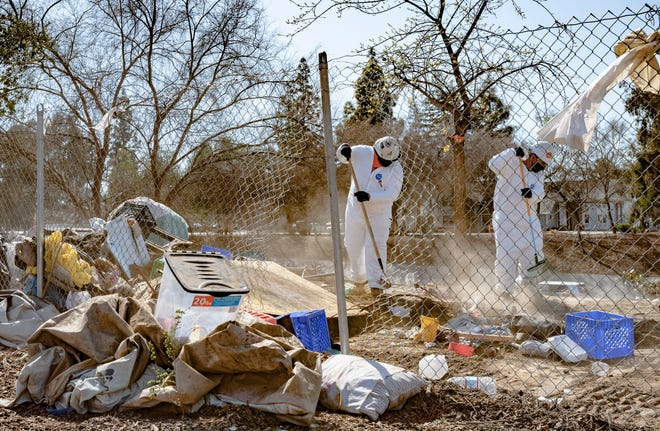 Workers clear debris Friday, February 26, 2021 along northbound Highway 99 near the Prosperity Avenue exit in Tulare. Most of the items were from homeless encampments in the area.