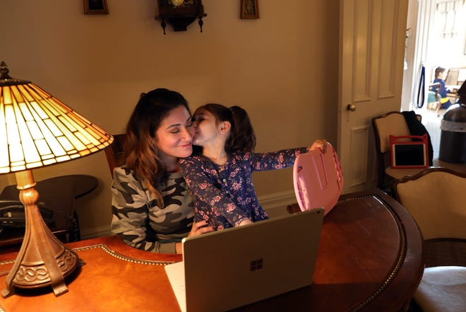 Leslie Chiaramonte gets a kiss from her daughter Phoenix, 3, at the Nardone Funeral Home, the family business in Peekskill, Feb. 25, 2021. Leslie quit her job as a nurse last fall because of hybrid learning to stay home with her two children. Now, she is pursuing her funeral director license so she can help her husband out in the family business.