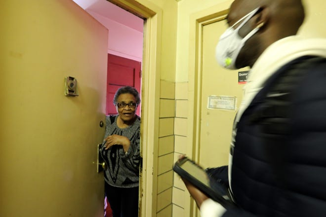 Marilyn Lucas, 84, tells Nelson Washington with the Bronx Rising Initiative that she's not ready to get the COVID-19 vaccination Feb. 24, 2021 at a Highbridge Gardens public housing building in the Bronx, New York.