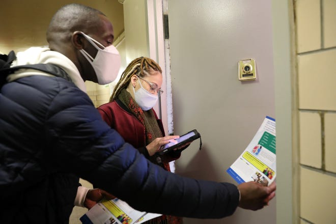 Lynmarie Francisco and Nelson Washington with the Bronx Rising Initiative go door-to-door registering residents for the COVID-19 vaccination at a Highbridge Gardens public housing building in the Bronx, New York, on Feb. 24, 2021.