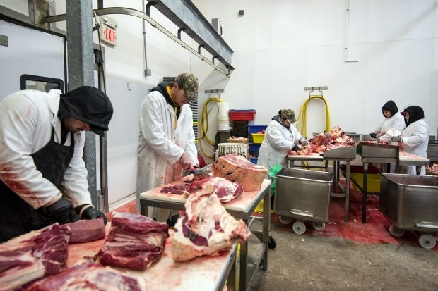 Workers cut pieces of meat Monday, Feb. 8, 2021, at Sailer's Food Market and Meat Processing in Elmwood, Wis.