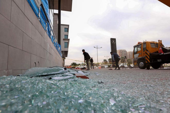 On Feb. 16, 2021, a worker cleans shattered glass outside a damaged shop following a rocket attack the previous night in Erbil, the capital of the northern Iraqi Kurdish autonomous region. The U.S. military struck facilities in eastern Syria used by Iran-backed militants believed responsible.