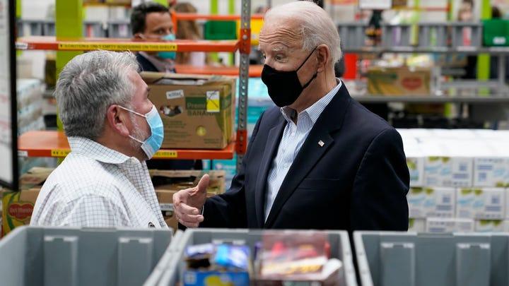 President Joe Biden talks with a volunteer at the Houston Food Bank, Friday, Feb. 26, 2021, in Houston.