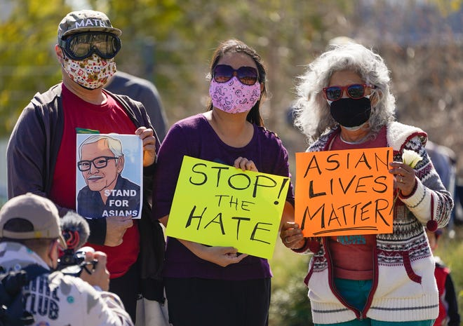 A man holds a portrait of late Vichar Ratanapakdee, left, an 84-year-old immigrant from Thailand, who was violently shoved to the ground in a deadly attack in San Francisco, during a community rally to raise awareness of anti-Asian violence and racist attitudes, in response to the string of violent racist attacks against Asians during the pandemic, held at Los Angeles Historic Park near the Chinatown district in Los Angeles, Saturday, Feb. 20, 2021.
