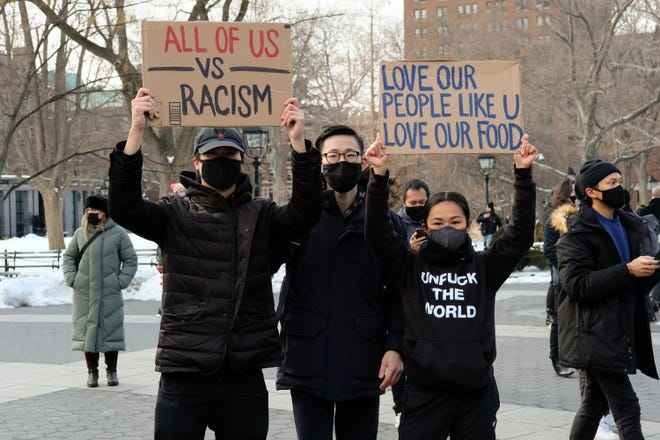 """Protesters hold signs that read """"all of us vs racism"""" and """"love our people like u love our food"""" at the End The Violence Towards Asians rally in Washington Square Park on Feb. 20, 2021, in New York City."""