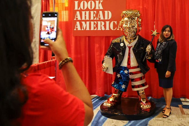 A woman takes a photo with a golden Donald Trump statue at the Conservative Political Action (CPAC) conference on Friday, Feb. 26, 2021, in Orlando, Fla. (Sam Thomas/Orlando Sentinel via AP) ORG XMIT: FLORL801