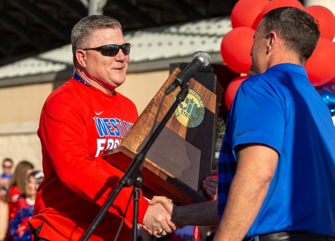 Westlake's Todd Dodge, receiving a trophy from Principal Steve Ramsey, was named Class 6A coach of the year by the Texas Sports Writers Association after guiding the Chaparrals to the 6A Division I state championship.