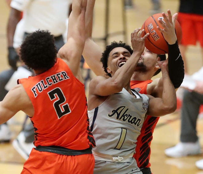 University of Akron guard Loren Cristian Jackson tries to shoot  two between Bowling Green's Josiah Fulcher and Chandler Turner as a foul is called on Turner during the first half of the Zips 83-71 loss Friday night at Rhodes Arena. [Karen Schiely/Beacon Journal].