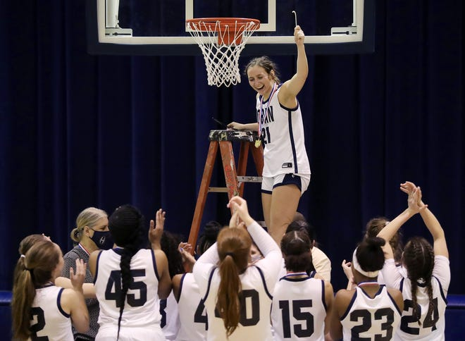 Teammates cheer as Hoban's Karli Anker holds up a piece of the net after the Knights defeated North Canton Hoover, 65-45, in the Division I district final, Friday, Feb. 26, 2021, in Akron, Ohio. [Jeff Lange/Beacon Journal]