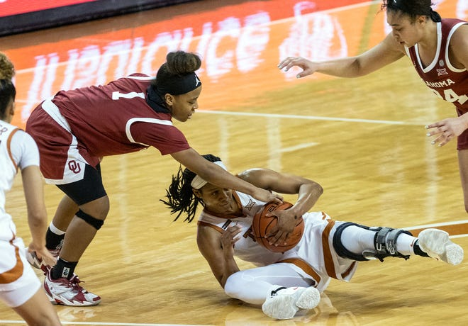 Texas' Kyra Lambert grabs a loose ball as Oklahoma's Nevaeh Tot reaches in and Skylar Vann watches at the end of the first half of the Sooners' victory Saturday at the Erwin Center.