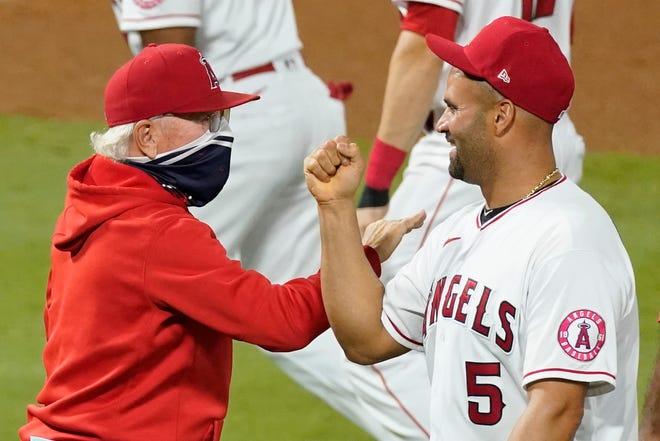 Los Angeles Angels' Albert Pujols, right, celebrates with manager Joe Maddon after a game against the Texas Rangers on Sept. 19 in Anaheim, Calif.