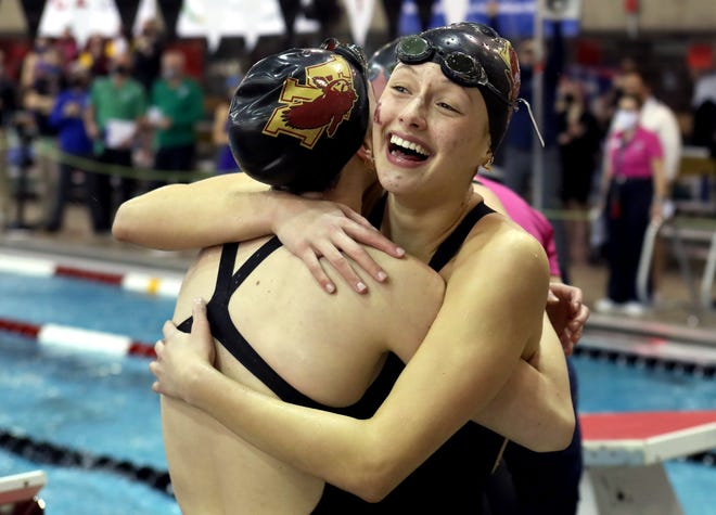 New Albany's Olivia Hovorka, right, hugs teammate Carly Meeting after the Eagles won the 400-yard freestyle relay to capture their first state championship on Friday.