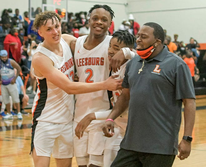 Leesburg's Brandon Barry (23), Camerin James (2), and Devin Graham (3) celebrate after winning the Class 5A-Region 2 championship game against Rockledge Friday at The Hive in Leesburg. [PAUL RYAN / CORRESPONDENT]
